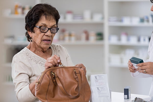 Close-up of an elderly woman opening her purse at the pharmacy counter talking to the pharmacist.