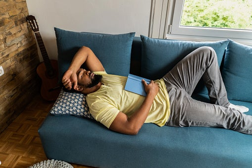 Young man taking a nap on the couch with her arm over his forehead and a book on his chest.
