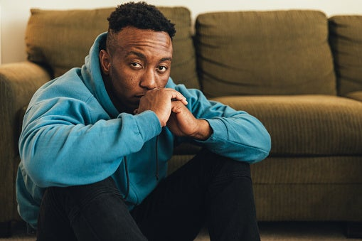 Young Black man in a teal blue sweatshirt sitting in front of a couch on the floor with a worried and sad expression.