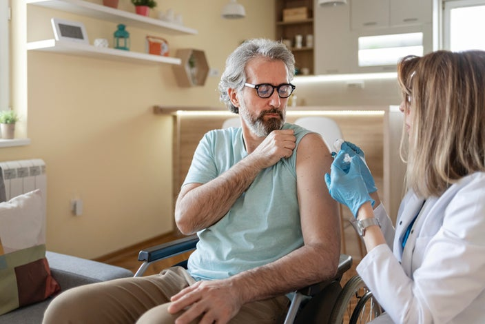 Doctor cleaning a male patient's arm with a cotton swab before giving him a shot while he sits in a wheel chair.