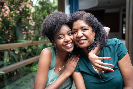 Portrait of a mother and daughter embracing while smiling and laughing