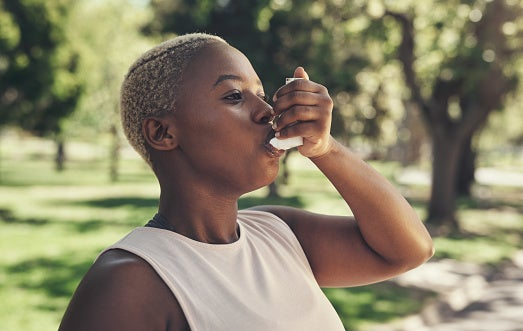 Young black woman with short hair outdoors using an inhaler.